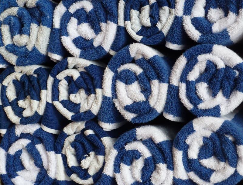Pila alta vicina di asciugamani blu e bianchi rotolati immagine stock