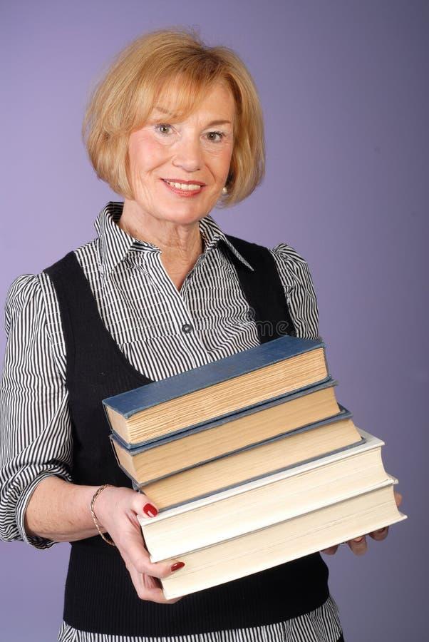Pila attraente delle strette della signora più anziana di libri fotografia stock libera da diritti