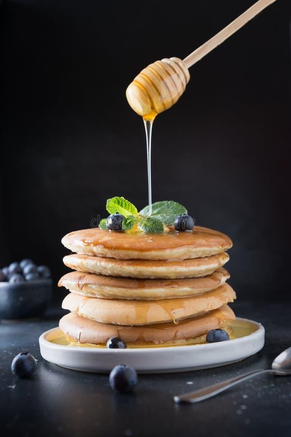 Pila casalinga dolce di pancake con il mirtillo, il miele e la menta freschi in piatto moderno sul nero fotografie stock