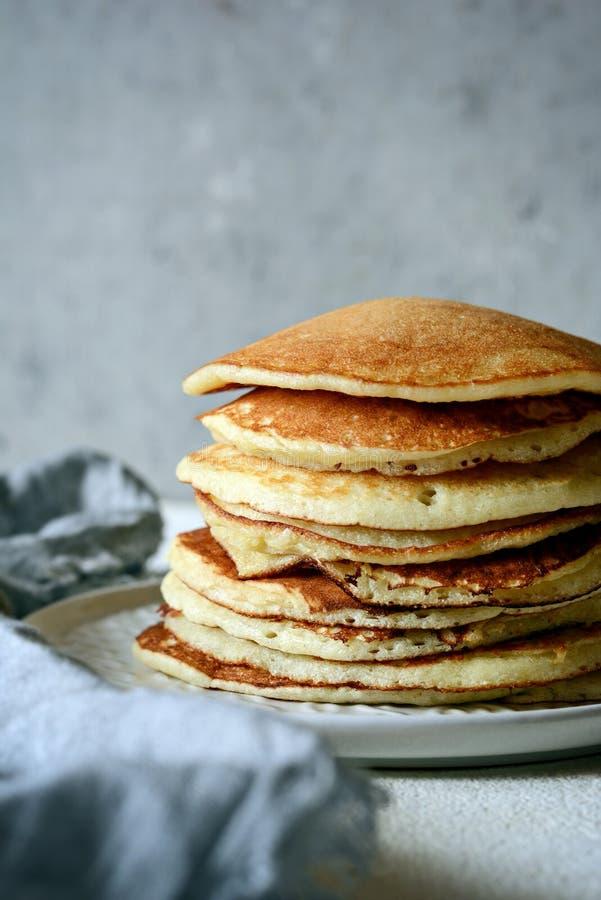 Pila casalinga dolce di pancake con miele per la prima colazione su un fondo grigio Bello brunch dolce della prima colazione fotografie stock libere da diritti