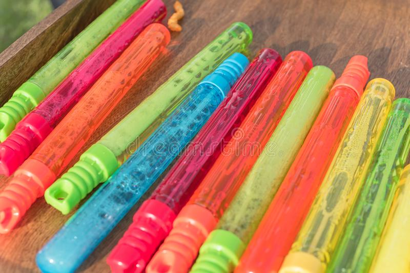 Pila colorida de varas plásticas de la burbuja en el primer de madera del fondo imagen de archivo