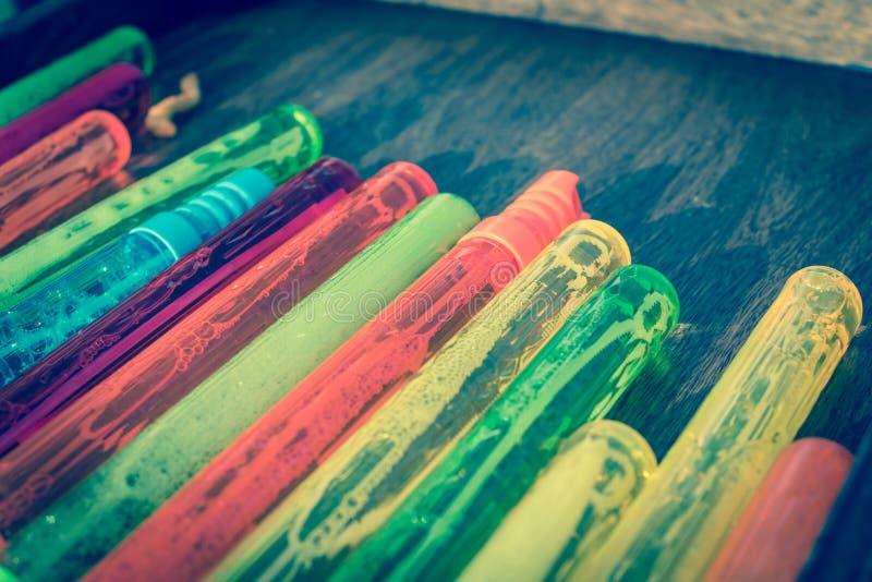 Pila colorida filtrada de la imagen de varas plásticas de la burbuja en el primer de madera del fondo foto de archivo