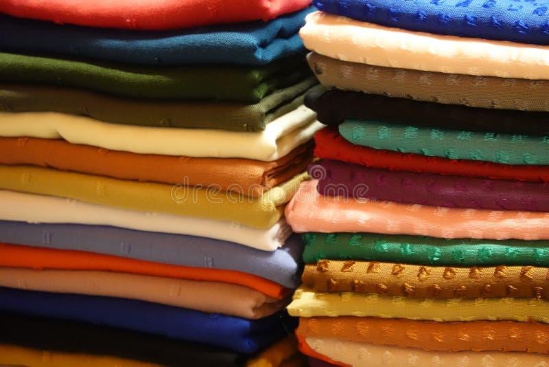 Pila con los paños y tela en muchos diversos colores en un st fotografía de archivo libre de regalías