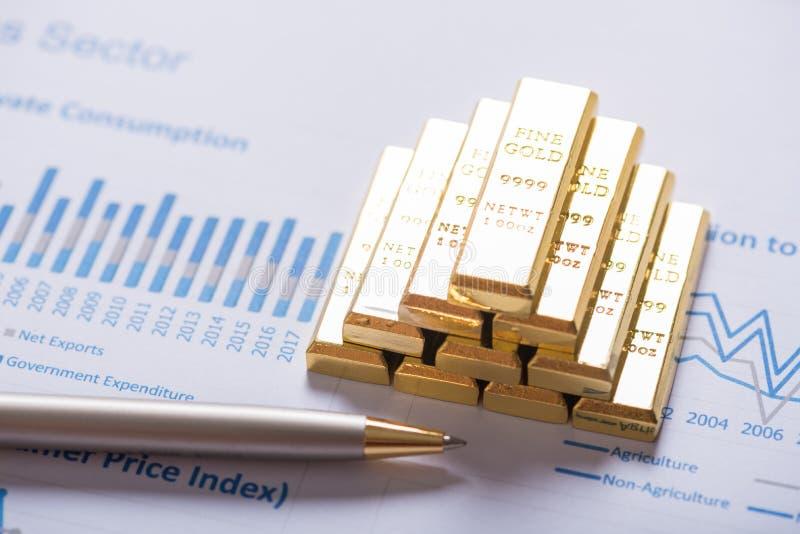Pila de barra de oro en fondo del gráfico del análisis de negocio fotografía de archivo libre de regalías
