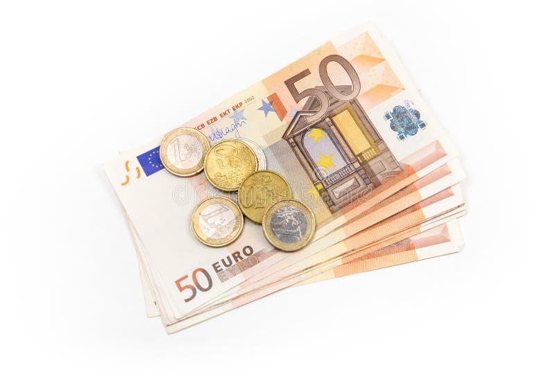 Pila de billetes de banco euro y de monedas aislados 50 billetes de banco euro imagenes de archivo