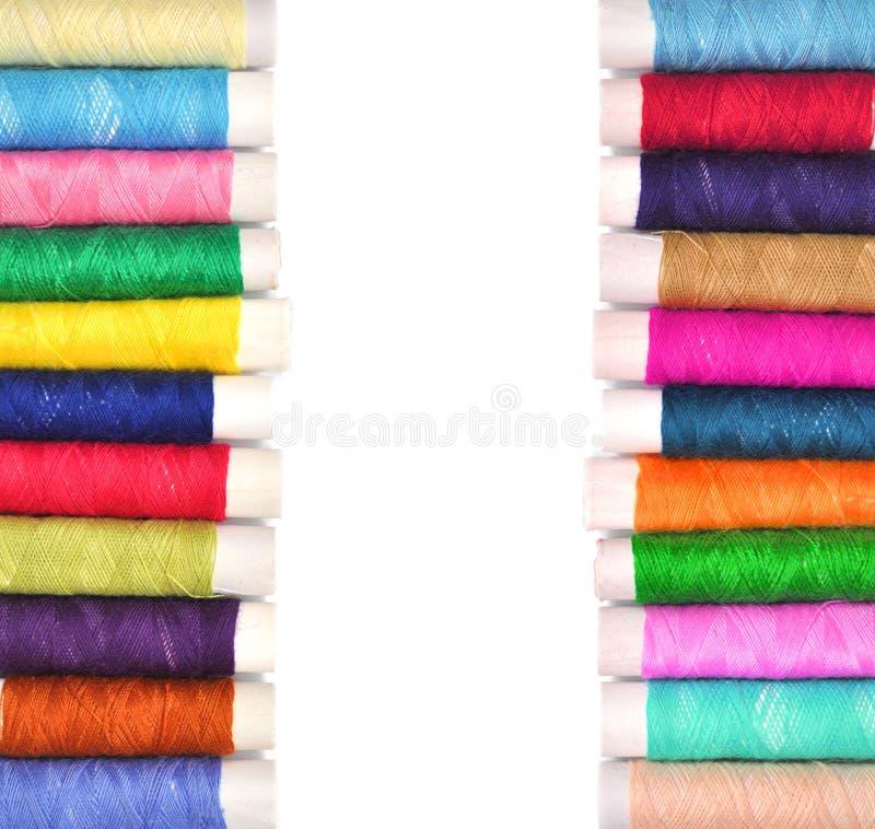 Pila de bobinas coloreadas del hilo del lurex aisladas en blanco fotos de archivo libres de regalías