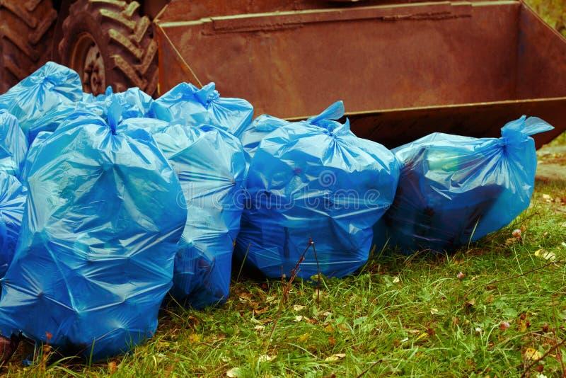Pila de bolsos de basura azules llenados de basura en la hierba y el cubo del tractor imagen de archivo libre de regalías