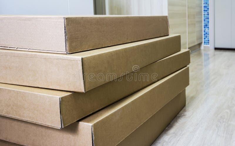 Pila de caja acanalada marrón de los muebles en piso laminado fotografía de archivo