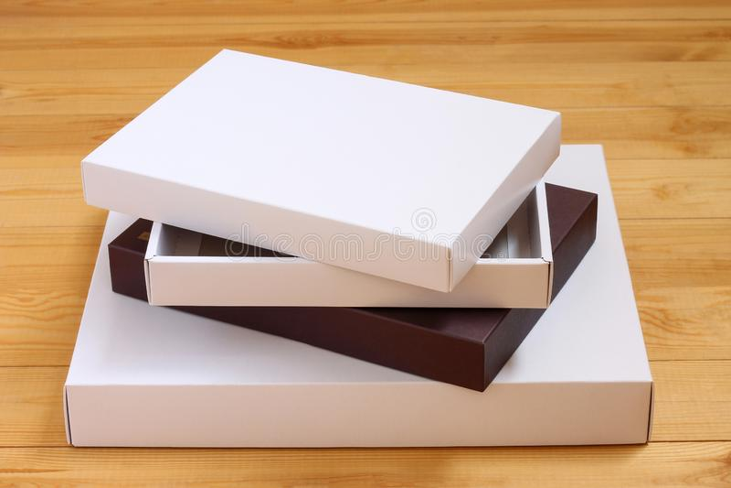 Pila de cajas en documento coloreado sobre fondo de madera imagenes de archivo