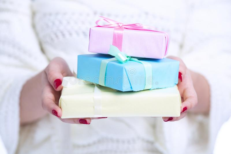 Pila de cajas de regalo en manos, mujer de la tenencia de la muchacha con los presentes envueltos en documento decorativo colorea fotos de archivo libres de regalías