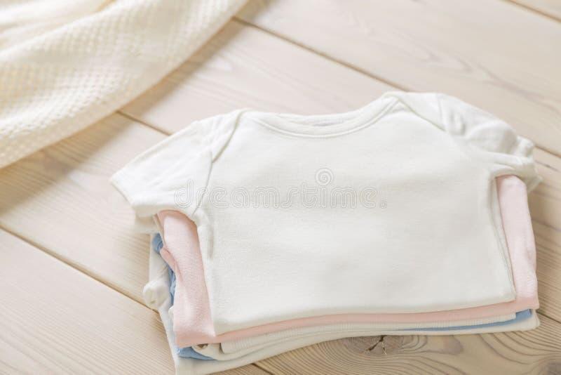 Pila de camisas del bebé fotos de archivo