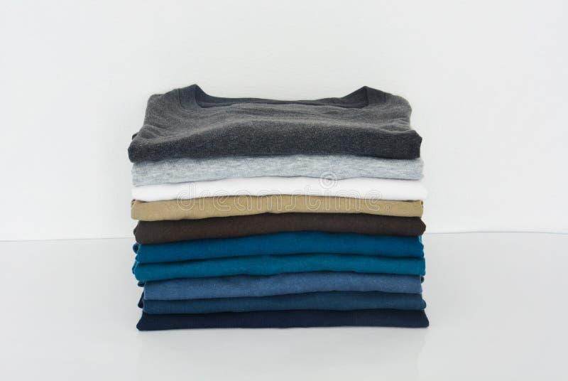 Pila de camiseta doblada en el fondo blanco foto de archivo
