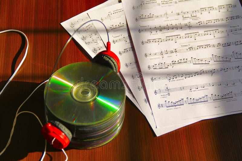 Pila de Cdes con el auricular y las notas musicales imagen de archivo libre de regalías