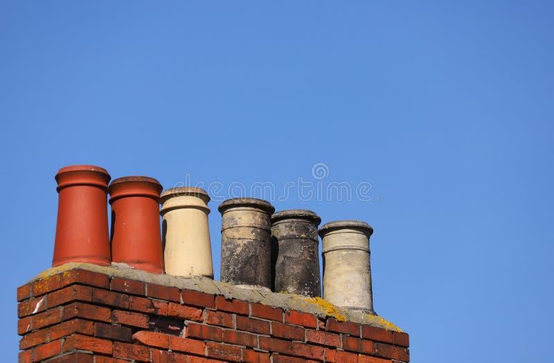 Pila de chimenea contra un cielo azul claro foto de archivo