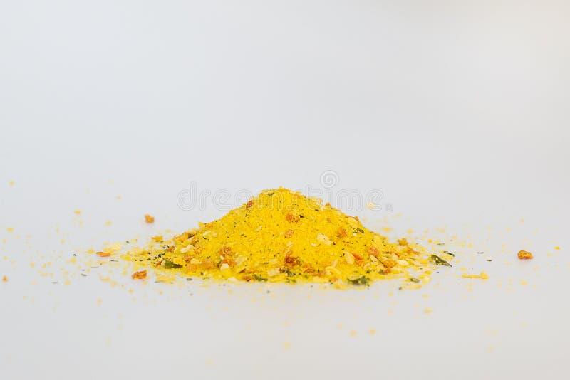 Pila de condimento universal en un cierre blanco del fondo para arriba El condimento contiene la sal y los pedazos de verduras se imagen de archivo