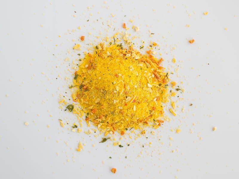 Pila de condimento universal en un cierre blanco del fondo para arriba El condimento contiene la sal y los pedazos de verduras se foto de archivo libre de regalías