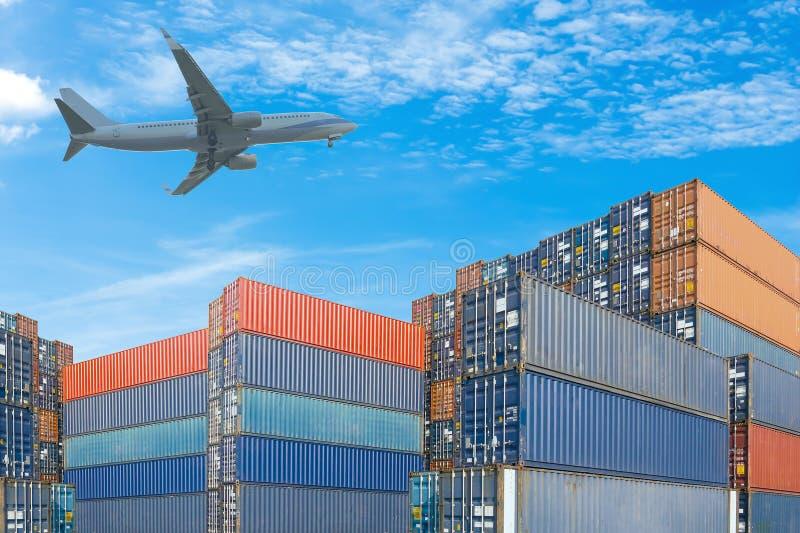 Pila de contenedores para mercancías con el avión en fondo del cielo azul fotografía de archivo