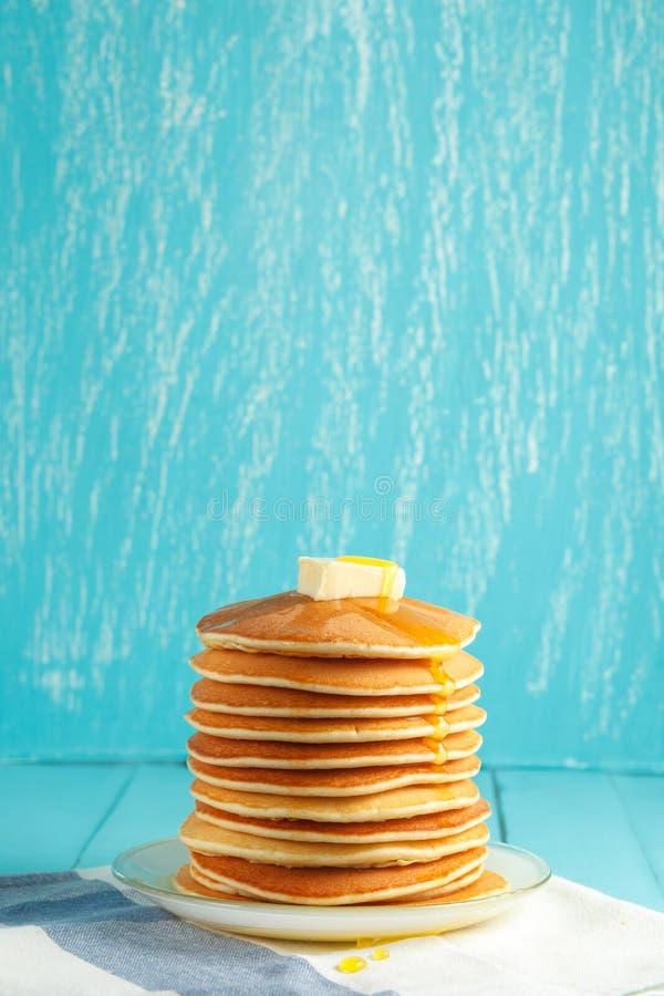 Pila de crepe con la miel y la mantequilla en el top fotografía de archivo libre de regalías