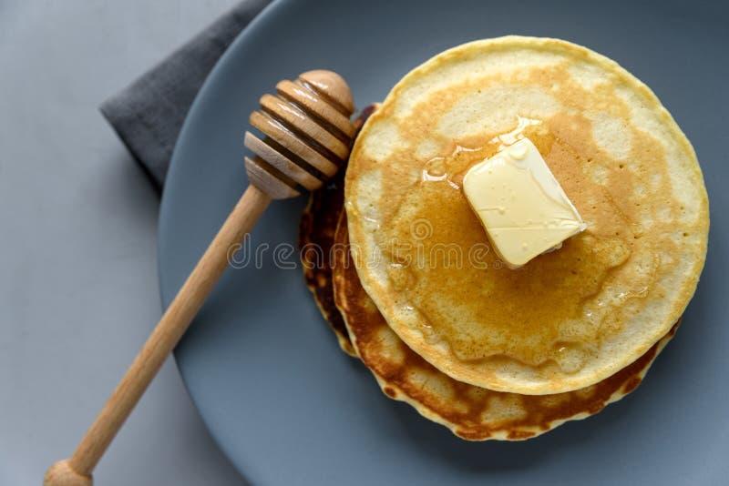 Pila de crepes con mantequilla y miel en fondo gris Foco selectivo Visión superior imagenes de archivo