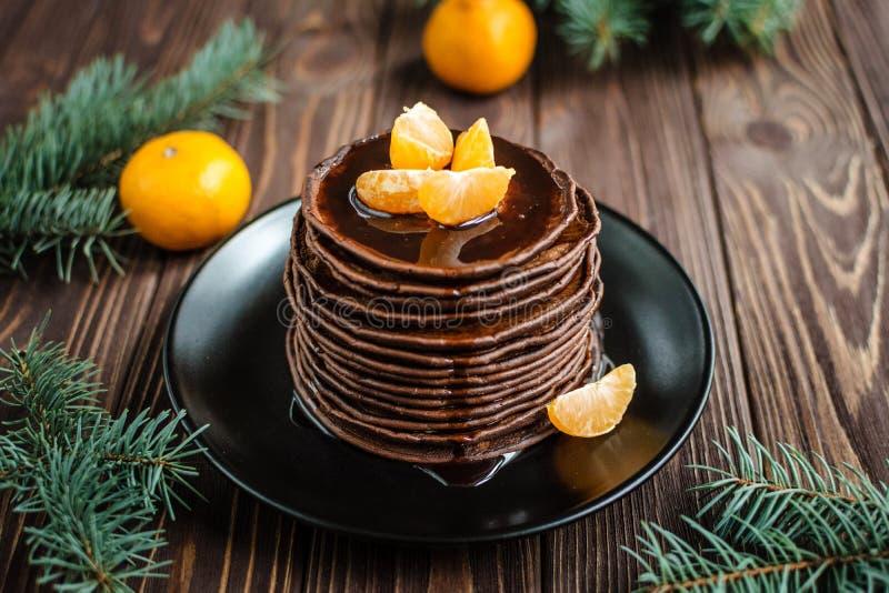 Pila de crepes del chocolate con el desmoche y las mandarinas del chocolate en fondo de madera imágenes de archivo libres de regalías