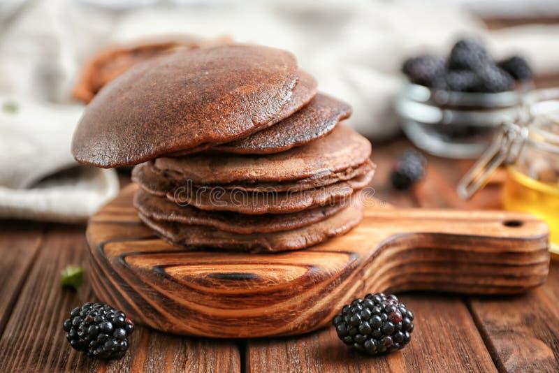 Pila de crepes deliciosas del chocolate en el tablero de madera foto de archivo libre de regalías