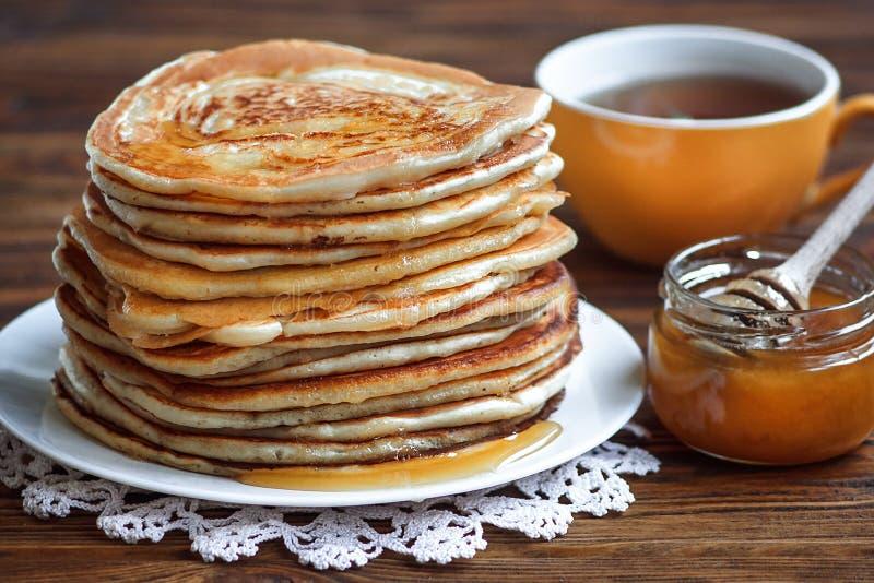 Pila de crepes deliciosas, hechas en casa con la miel en la placa blanca en fondo de madera Desayuno sano, cierre para arriba Día fotografía de archivo libre de regalías