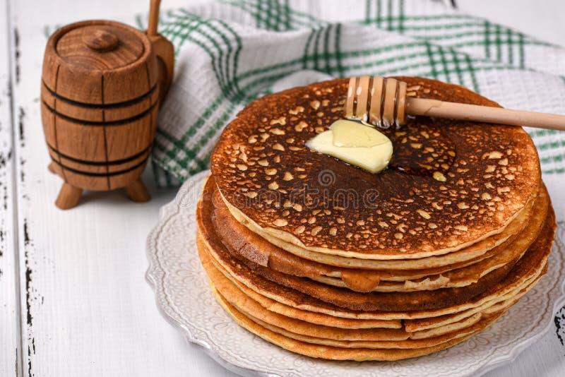 Pila de crepes sabrosas de la harina de maíz con mantequilla y miel para el desayuno fotos de archivo