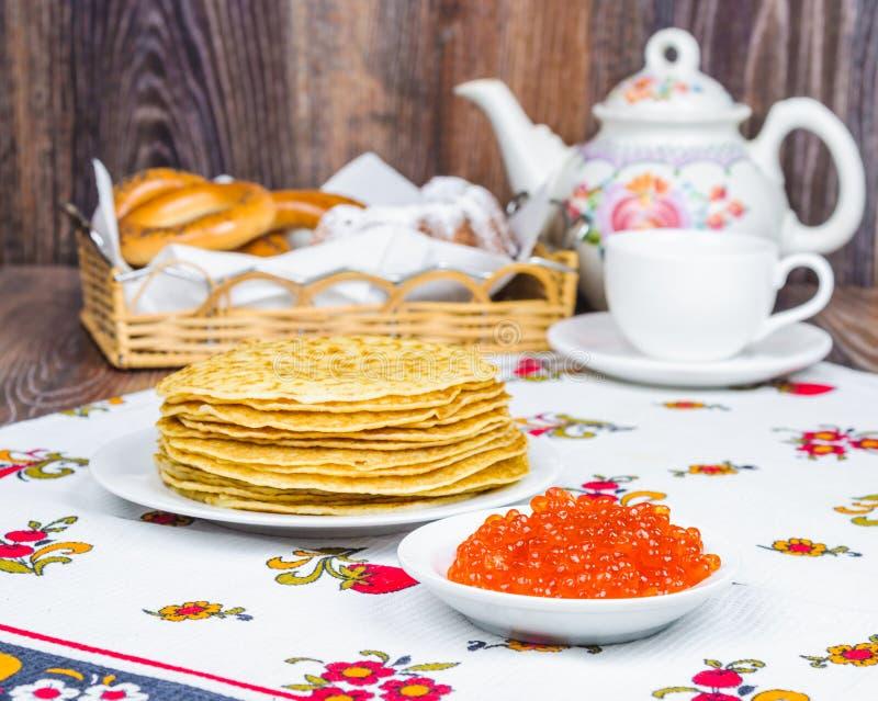 Pila de crepes y de caviar rojo imagenes de archivo
