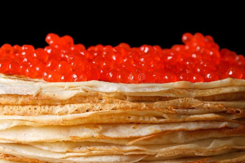 Pila de crespones con macro roja del caviar aislada en negro fotografía de archivo libre de regalías