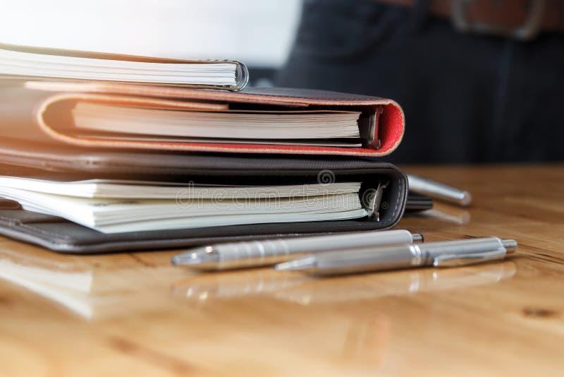 Pila de cuadernos y de plumas en el escritorio de oficina fotos de archivo