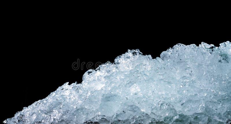Pila de cubos de hielo machacados en fondo oscuro con el espacio de la copia Primero plano machacado para las bebidas, cerveza, w fotos de archivo