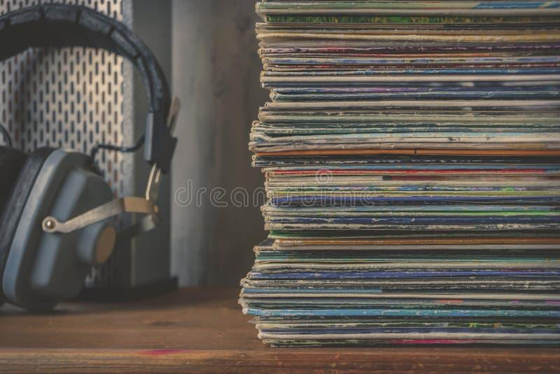 Pila de discos de vinilo y de auriculares viejos foto de archivo