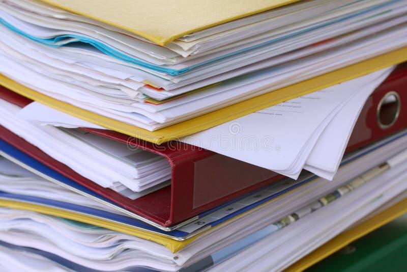 Pila de diversas carpetas de archivos o carpetas de anillo por completo con los documentos de la oficina imagen de archivo