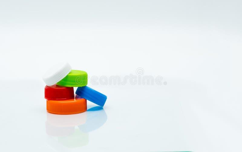 Pila de diversos tamaño y color de tapones de tuerca plásticos redondos imagenes de archivo