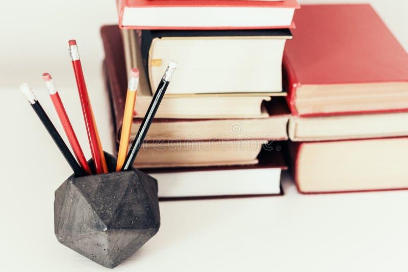 Pila de fondo del concepto de la educación del libro, de muchas pilas de los libros y de lápices en tenedor concreto en la tabla  imagen de archivo libre de regalías