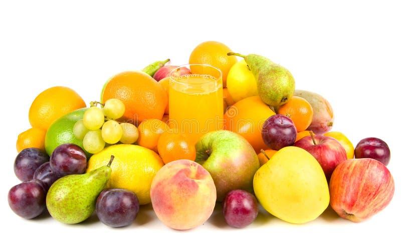 Pila de frutas alrededor de un vidrio de jugo fotografía de archivo libre de regalías