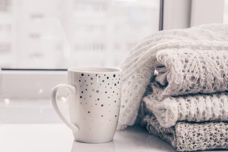 Pila de géneros de punto acogedores y de una taza de café en el alféizar de mármol blanco contra el fondo blanco de la ventana Co imagen de archivo