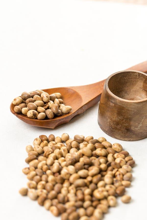 Pila de habas de soja con la cuchara de madera en la tabla de mármol blanca del fondo imagen de archivo