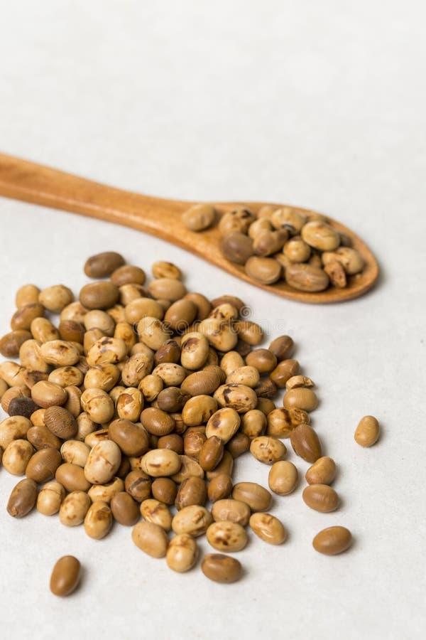 Pila de habas de soja con la cuchara de madera en la tabla de mármol blanca del fondo imagen de archivo libre de regalías