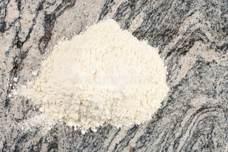 Pila de harina blanca en la tabla de mármol gris de la cocina imagenes de archivo