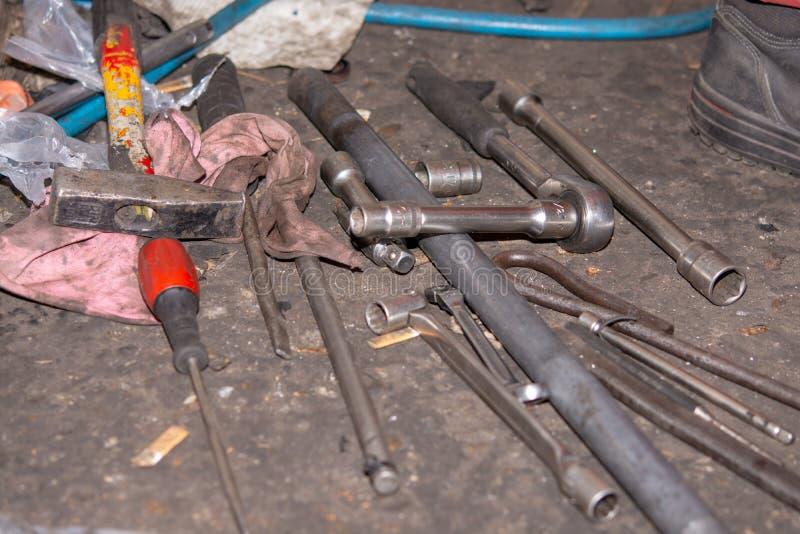 Pila de herramientas viejas y sucias en el taller del mecánico de coche Destornilladores y llave en el piso imagenes de archivo