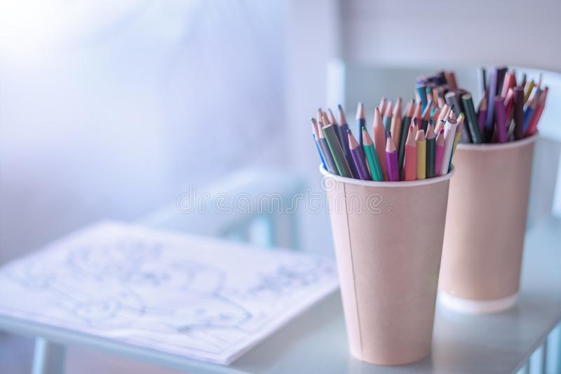 Pila de l?pices coloreados en un vidrio en el fondo de madera, visi?n superior Un lugar acogedor a dibujar para los niños imagen de archivo