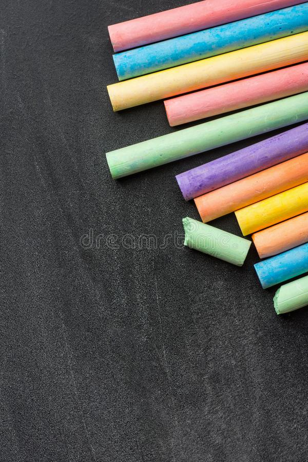Pila de la fila de creyones multicolores de las tizas en la pizarra rasguñada oscuridad De nuevo a diseño gráfico de la creativid imágenes de archivo libres de regalías
