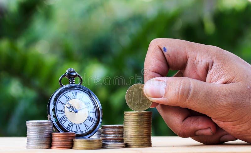 Pila de la moneda del dinero dispuesta como gráfico en la tabla y la alarma de madera c imagen de archivo libre de regalías