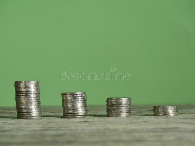 Pila de la moneda que crece la tabla de madera fotografía de archivo
