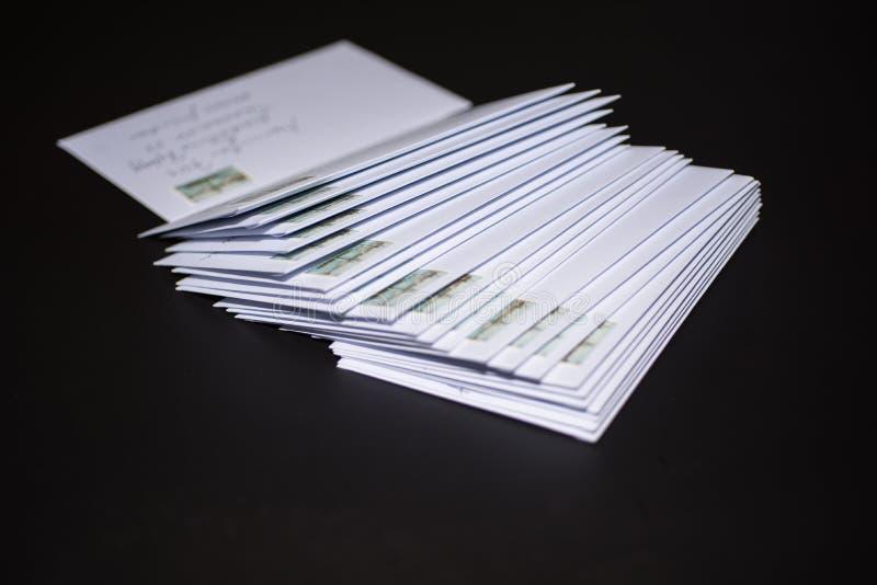 Pila de letras franqueadas en los sobres blancos en fondo negro fotos de archivo libres de regalías