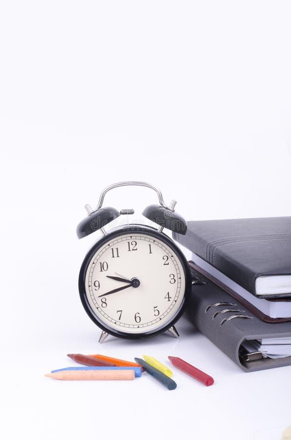 Pila de libro con el reloj del vintage que hace tictac y el creyón colorido en la tabla blanca fotos de archivo