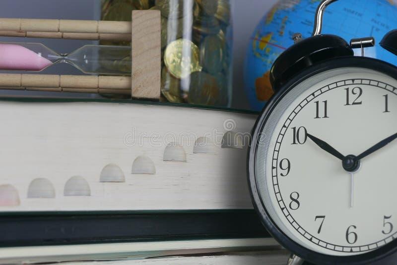 Pila de libro con reloj de arena, el globo, el tarro de monedas, y el reloj Dinero, tiempo, mundo y concepto de la educación fotos de archivo