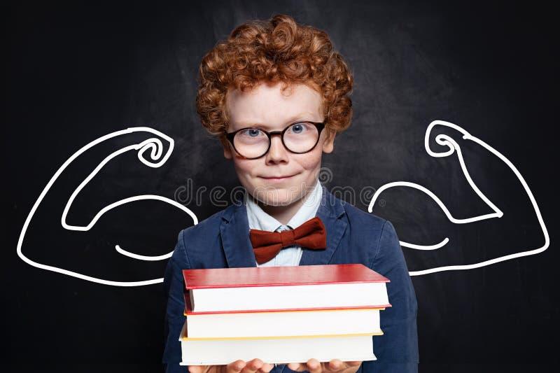 Pila de libro elegante de la tenencia del estudiante del niño divertido en fondo de la pizarra De nuevo a concepto de la escuela foto de archivo libre de regalías