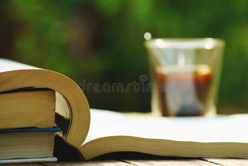 Pila de libro y taza de café en la tabla de madera en el color de tono del vintage, concepto de la sabiduría, espacio de la copia fotografía de archivo libre de regalías